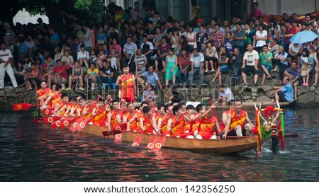 FOSHAN CITY JUNE 14: The dragon boat race held once a year in Foshan River, 16 dragon boat teams from Foshan everywhere to participate in the race June 14, 2013 in Foshan, China - stock photo