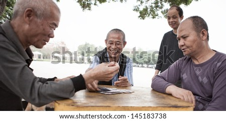 FOSHAN, GUANGDONG/CHINA - MARCH 17: Unidentified men playing cards in Shishan Huaxi Park, Shunde District of Foshan City, Guangdong Province, China on March 17th, 2013.  - stock photo