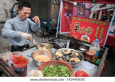 FOSHAN, GUANGDONG/CHINA - MARCH 16: Unidentified street food vendor prepares food in Shunde District of Foshan City, Guangdong Province in Southern China on March 16h, 2013. - stock photo