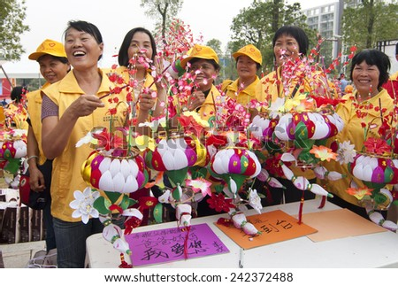 FOSHAN - Nov 1:Paper lanterns sale activities organised by the government in a lake, all money go to welfare homes, selling the volunteer work very hard Nov 1, 2014 in FOSHAN, China - stock photo