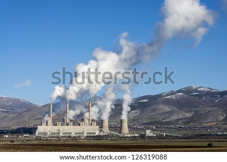 Fossil fuel power plant in full operation, emitting smoke. - stock photo