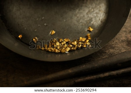 Found gold. gold panning or digging. Gold on wash pan. Intentionally shot with low key shadows and shallow depth of field. - stock photo