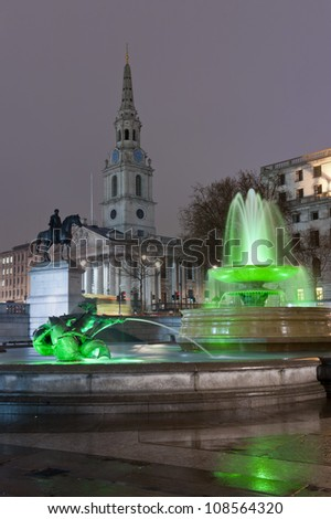 fountain and the church of st martin in the field, at trafalgar square, by night - stock photo