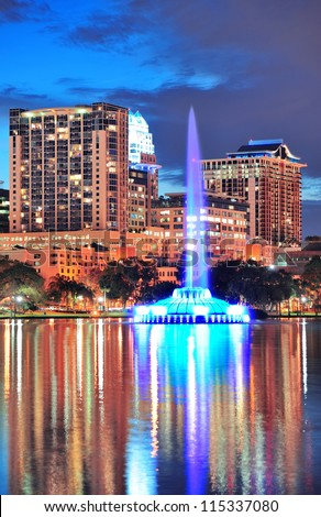 Fountain closeup with Orlando downtown skyline over Lake Eola at dusk with urban skyscrapers and lights. - stock photo