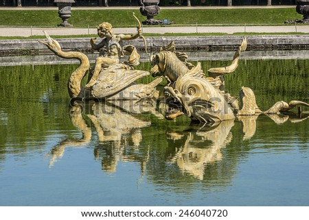 Fountain in gardens of famous Versailles palace. Palace of Versailles was a royal chateau. It was added to UNESCO list of World Heritage Sites. Paris, France. - stock photo