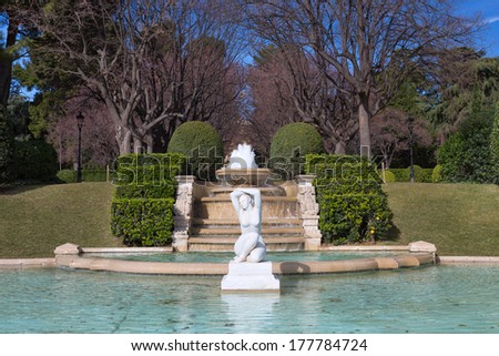 Fountain in the park on a background of the fence. - stock photo