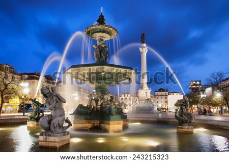 Fountain on Rossio Square at night in Lisbon, Portugal. Baroque style artwork with mythical creatures sculptures. Column of Dom Pedro IV in the background.