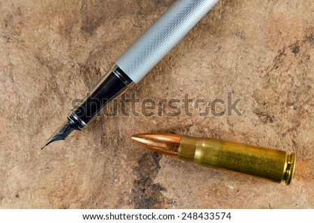 Fountain pen and a bullet on vintage background - stock photo