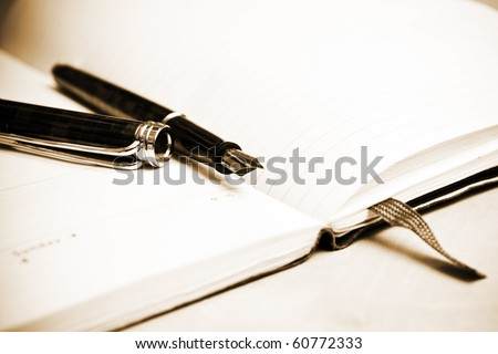 Fountain pen and calendar in composition in sepia tone - stock photo