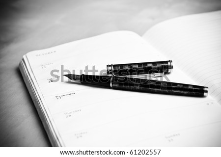 Fountain pen and calendar with date in composition in black and white - stock photo