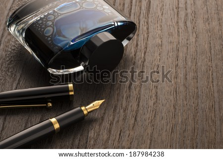 fountain pen and ink bottle on table - stock photo