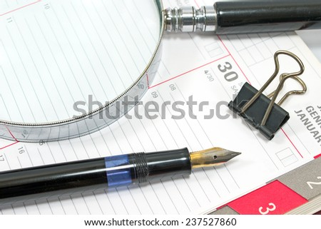 Fountain pen and magnifying glass on personal organizer - stock photo