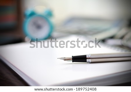 Fountain pen and  notebook on table - stock photo
