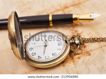 fountain pen and pocketwatch on old sheet - stock photo