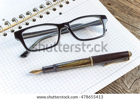 Fountain pen and spiral notebook with eyeglasses