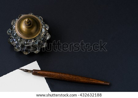Fountain pen, inkwell on a black textured - stock photo