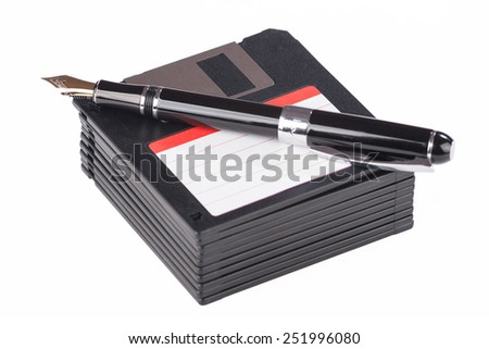 fountain pen lying on a pile of floppy disks over white - stock photo
