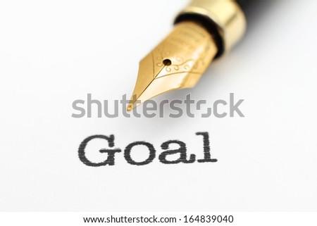 Fountain pen on goal text - stock photo