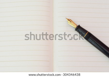 Fountain pen on lined paper book - stock photo