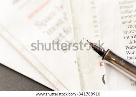 Fountain pen on newspaper - stock photo