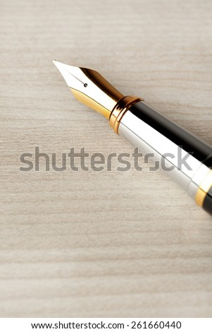 Fountain pen on wooden table background - stock photo