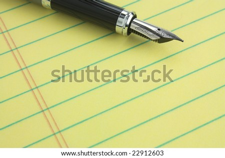 Fountain pen on yellow legal pad of paper - add your business message - stock photo