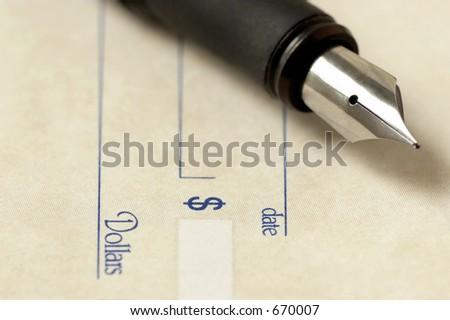 Fountain pen over check - stock photo