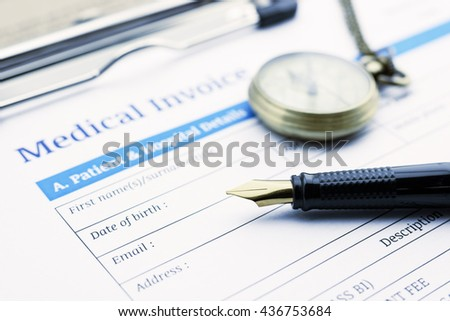 Fountain pen, pocket watch and a medical invoice on a clipboard. - stock photo