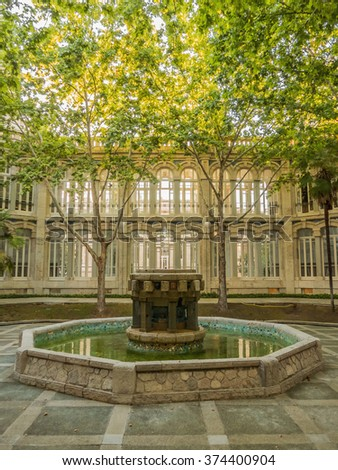 Fountain surrounded by trees in park area - stock photo