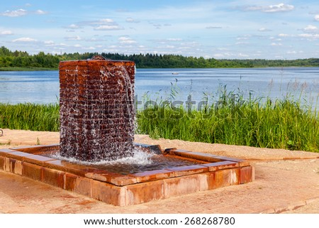 Fountain with drinking water at the lake in summer sunny day - stock photo