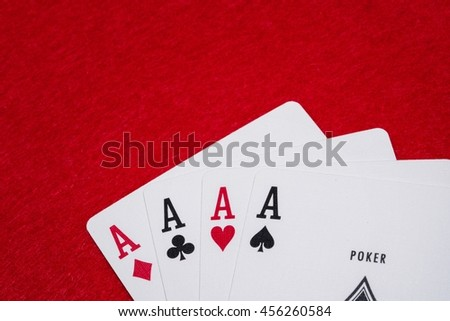 Four aces - A winning poker hand of four aces playing cards suits on RED. - stock photo