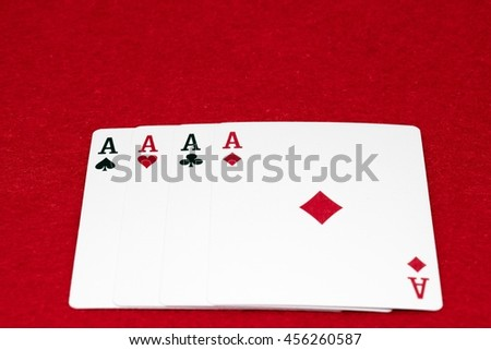 Four aces - A winning poker hand of four aces playing cards suits on RED.