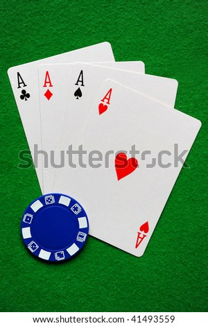 Four Aces and a blue poker chip - stock photo