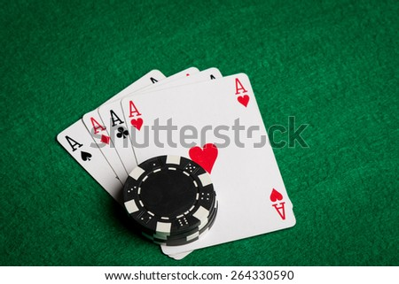 four aces and black chips on a green table - stock photo