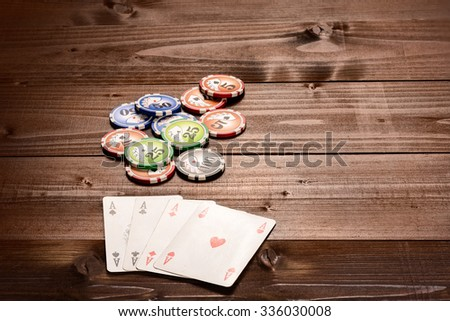 Four aces and chips, vintage poker game playing cards on a wood table - stock photo