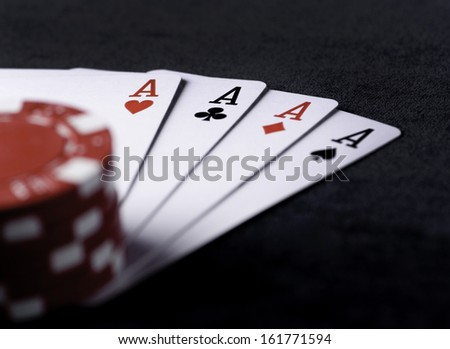 four aces high on black table with chips on black background - stock photo