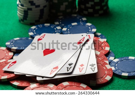 four aces on color poker chips on green table - stock photo