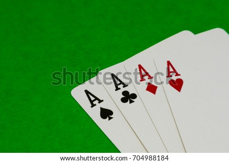 Four aces on green background.