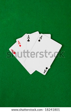 Four aces on green poker table.