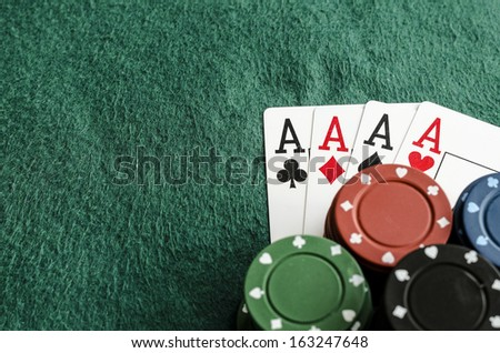 four aces with casino chips on green table cloth copy space - stock photo
