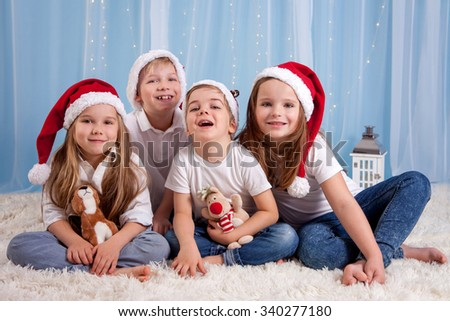 Four adorable kids, preschool children, having fun for christmas, studio shot - stock photo