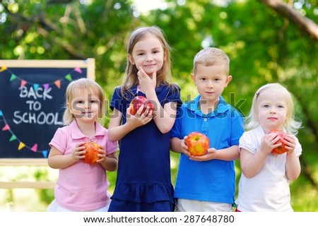 Four adorable little kids feeling very excited about going back to school - stock photo