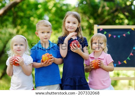 Four adorable little kids holding healthy organic apples in summer park on beautiful sunny day - stock photo