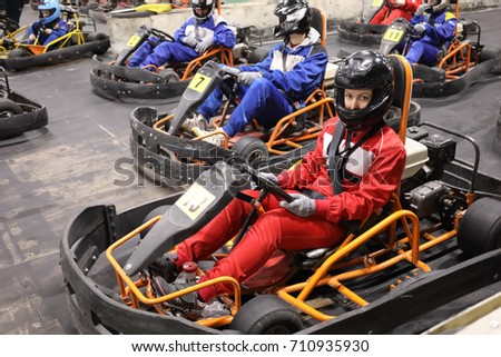 Four adults and two children prepare for driving karting, focus on right woman in red