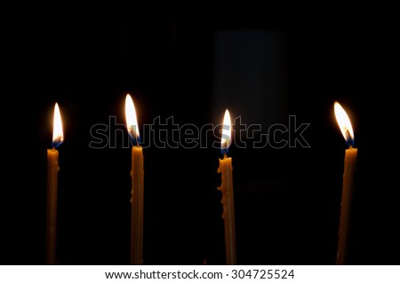 four alight candles over the black background - stock photo