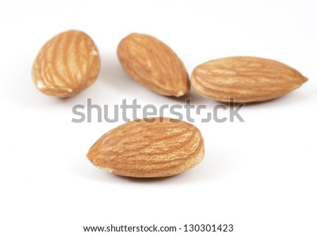 Four almonds on white background with a selective focus on the foreground almond
