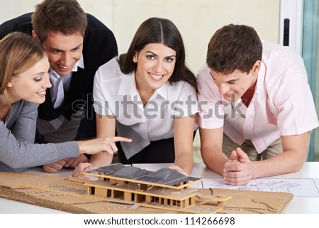 Four architects discussing a 3D house draft in their office - stock photo