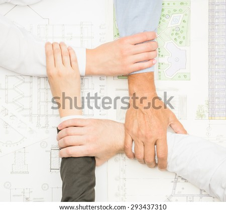Four architects sitting around a table and putting hands together. Close-up. - stock photo