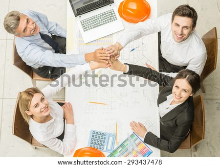 Four architects sitting around a table and putting hands together. Team work. - stock photo