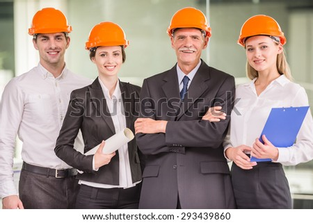 Four architects standing at modern office and looking at camera. Team work concept. - stock photo